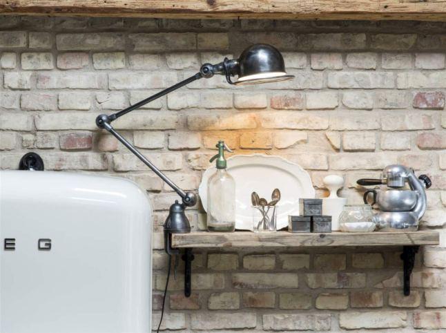 Неоштукатуренная кирпичная стена, полочка из состаренного дерева и винтажный светильник являются неотъемлемой частью стиля лофт