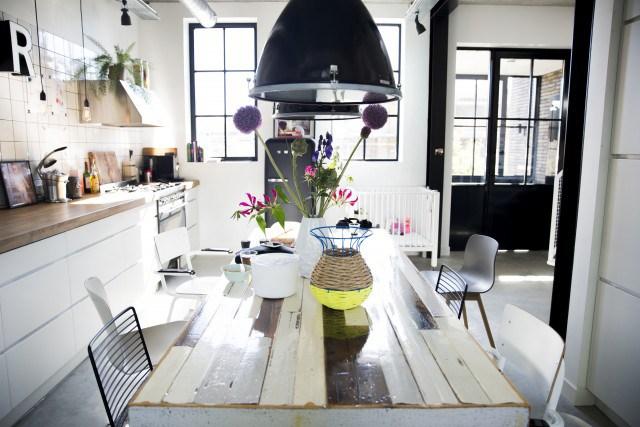 Дизайн кухни выполнен в стиле лофт с характерными плафонами, столом вытяжкой и открытыми вентиляционными трубами.