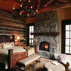 Атмосфера сельского дома с камином в спальне.