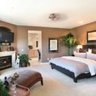 Большая и светлая спальня с камином в углу комнаты под телевизором.