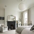 Черный камин отчетливо выделяется в интерьере светлой спальни.