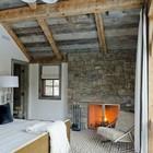 Эклектичная, но очень уютная спальня с намеком на французскую деревню. Дизайн камина отлично сочетается с креслом и прикроватным светильником.