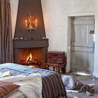 Если вам нравится атмосфера древнего замка, то вы должны оценить эту спальню. Причудливый подсвечник над камином, ветхая и простая дверь и шкуры на полу создают неповторимую атмосферу здания с историей.