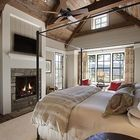 Спальня в деревенском стиле с каменным камином.