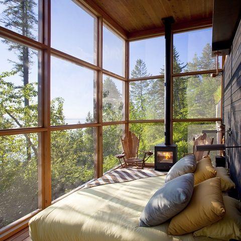 Отдельно стоящий стальной камин современного дизайн отлично впишется в спальню с остекленными стенами.