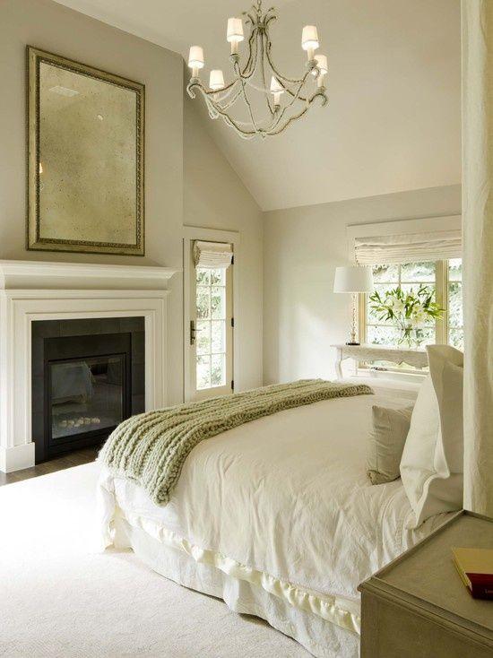 Спальня решенная в нейтральной цветовой гамме с камином.