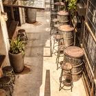 Задний двор ресторана с бочками-столами и барными стульями. (на открытом воздухе,патио,балкон,терраса,архитектура,дизайн,экстерьер,индустриальный,лофт,винтаж,стиль лофт,индустриальный стиль,мебель)