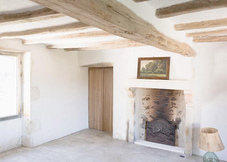 Действующий камин в спальне на первом этаже. Деревянные конструкции перекрытия оставлены открытыми.
