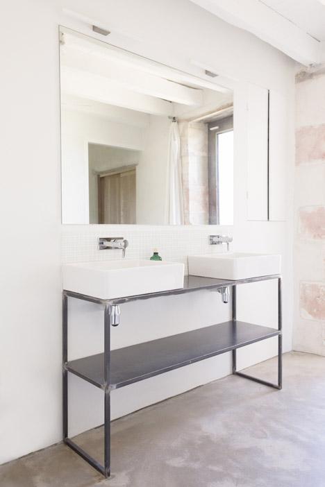 Индустриальная простота грубо свареной основы умывальника и большое зеркало в ванной отлично гармонируют с деревенским стилем дома.