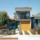 Фасад дома с гаражом и паковочным местом перед ним.