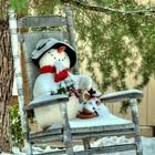 Снеговик в старом кресле-качалке перед домом.