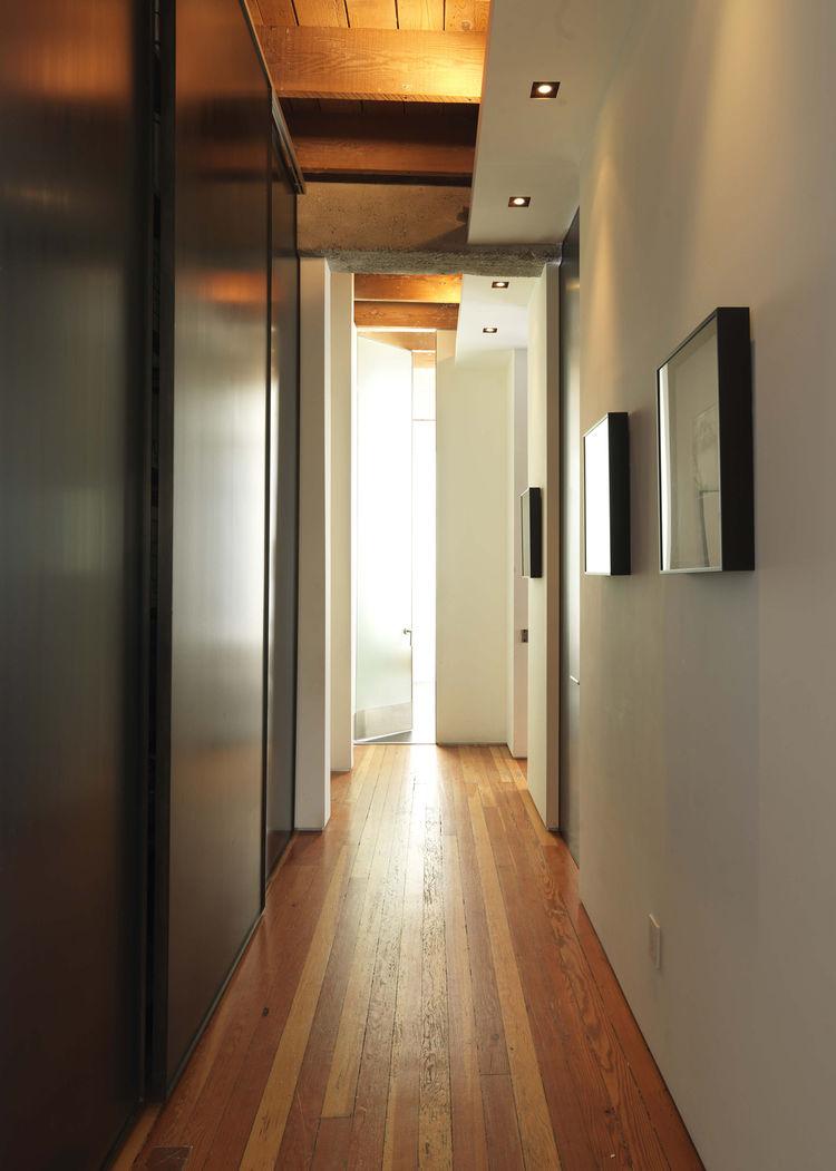 Длинный коридор отделяет рабочие пространства от приватных и увеличивает расстояние между ними.
