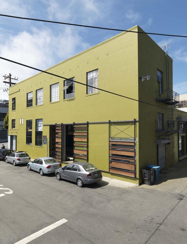 Фасад здания склада 1940-х годов, которое Сэнды спасли от сноса. Сдвижные ворота напоминают о промышленном прошлом здания, однако их дизайн и зеленый цвет фасада существенно оживляют здание.