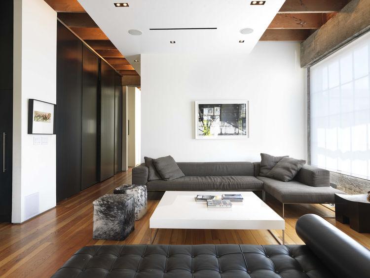 Открытая планировка, высокие потолки и белые стены - все способствует хорошей освещенности гостиной, где атмосферу формируют диван Барселона дизайна Мис ван дер Роэ и две оттоманки Блайт Пони Кубэ от Гас Дизайн.