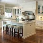 Большие мягкие табуреты у кухонного острова на традиционной кухне.
