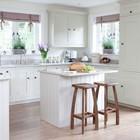 Две высокие деревянные табуретки у кухонного острова в белой кухне средиземноморского стиля.