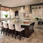 Элегантная кухня с мягкими барными креслами у кухонного острова.