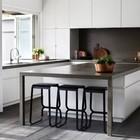 Металлические черные стулья в черно-белом интерьере минималистичной кухни.