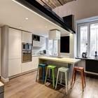 Разноцветные барные стулья дизайнера Ксавье Пошара в маленькой минималистичной кухне существенно оживляют интерьер.