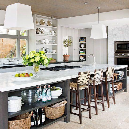 Элегантные деревянные барные стулья с плетеными сиденьями и спинками у большого кухонного острова на кухне средиземноморского стиля.