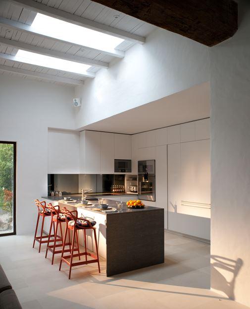 Красные барные стулья в серо-белой кухне.