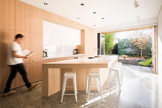 Однотонные белые стулья дизайна Ксавье Пошара в кухне с выходом на террасу.