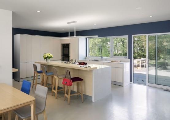 Современная белая минималистичная кухня в стиле середины 20-го века с разноцветными барными стульями, которые оживляют интерьер.