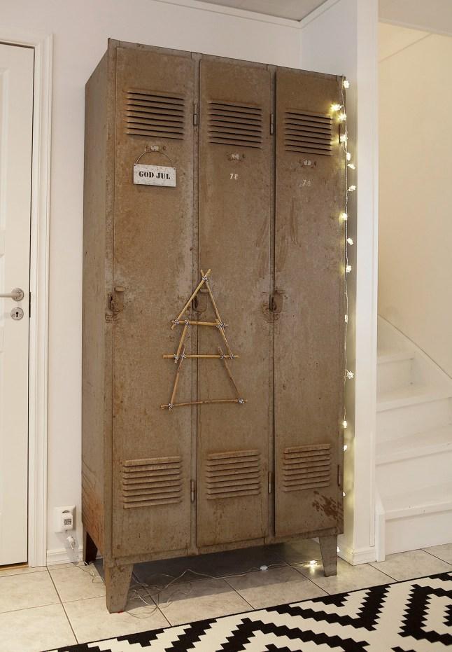 Металлический шкаф украшенный гирляндой и ёлочкой из проволоки выглядит очень индустриально.