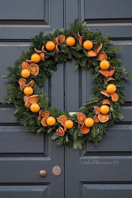 Рождественский венок украшенный ломтиками и целыми апельсинами.