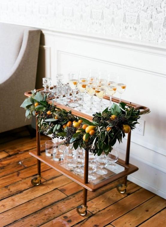 Сервировочный столик украшенный новогодней гирляндой с лимонами.