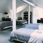 Большая спальня на мансарде с несколькими кроватями на колесах