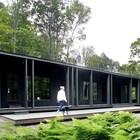 Черный фасад небольшого дома подчеркивает красоту и яркость окружающей зелени.