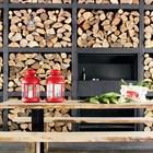 Стальное барбекю на террасе встроено в стальные стеллажи для хранения дров.