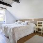 Маленькая спальня на мансарде фермерского дома. Отлично решено изголовье кровати.
