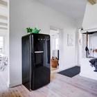 Старый очаг хоть и не используется по назначению, однако является важным элементом декора. Черный холодильник SMEG гармонично вписался в интерьер кухни рядом со старым очагом.