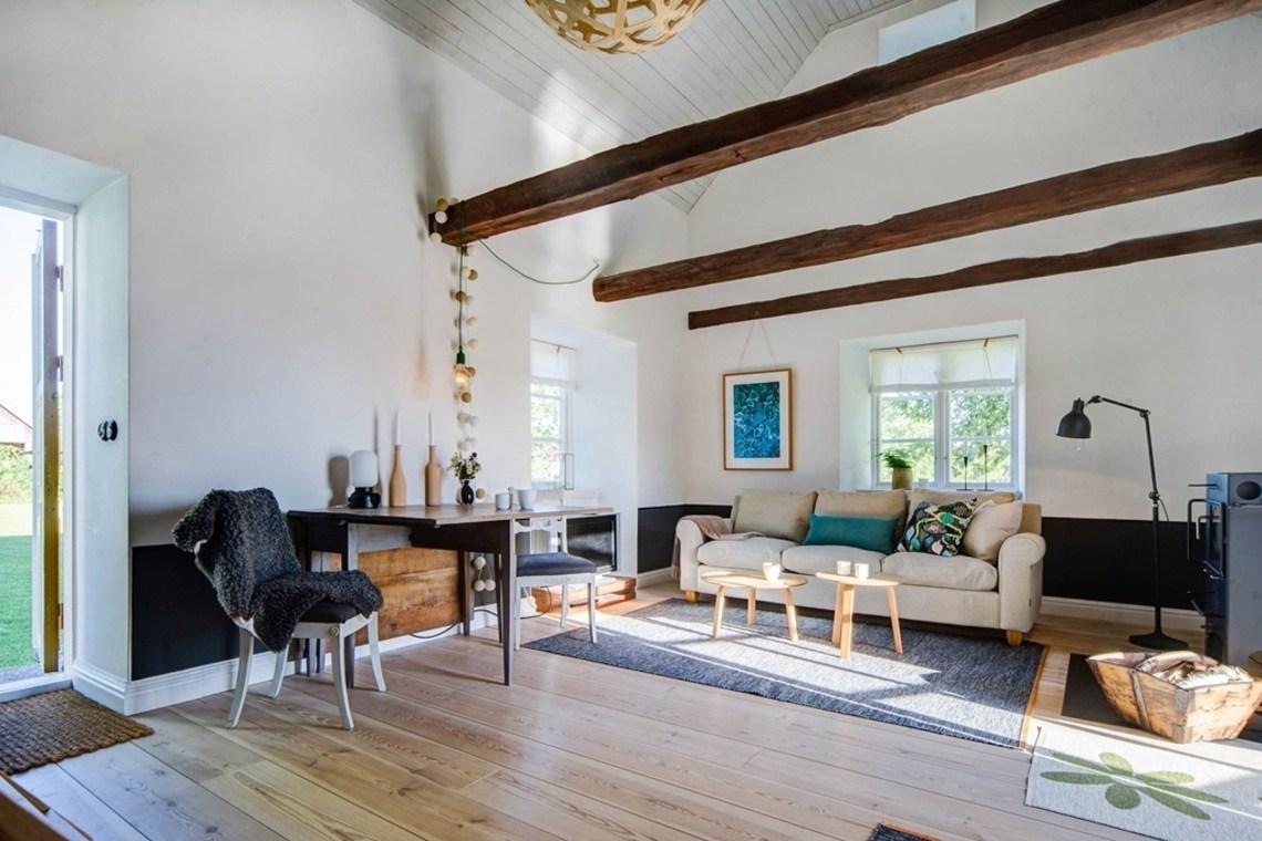 Гостевой дом. Гостиная со стальным камином и высоким потолком.