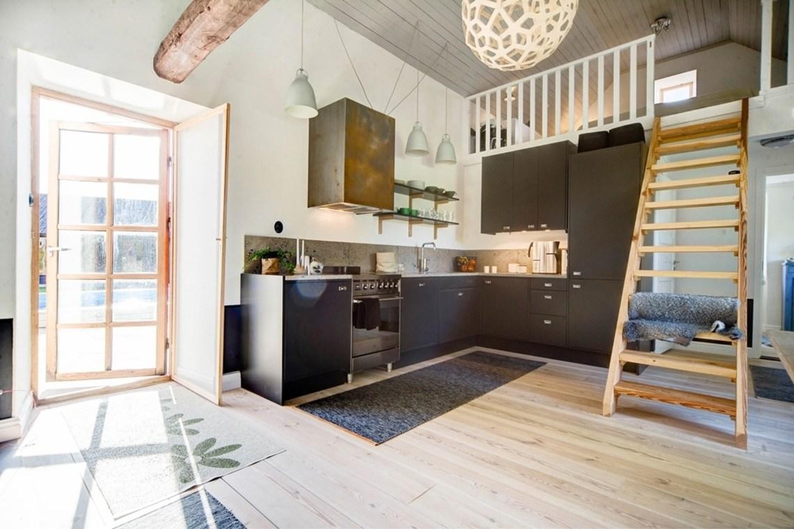 Гостевой дом имеет объединенное пространство кухни-столовой и гостиной, а на антресоли выполнена спальня-лофт.