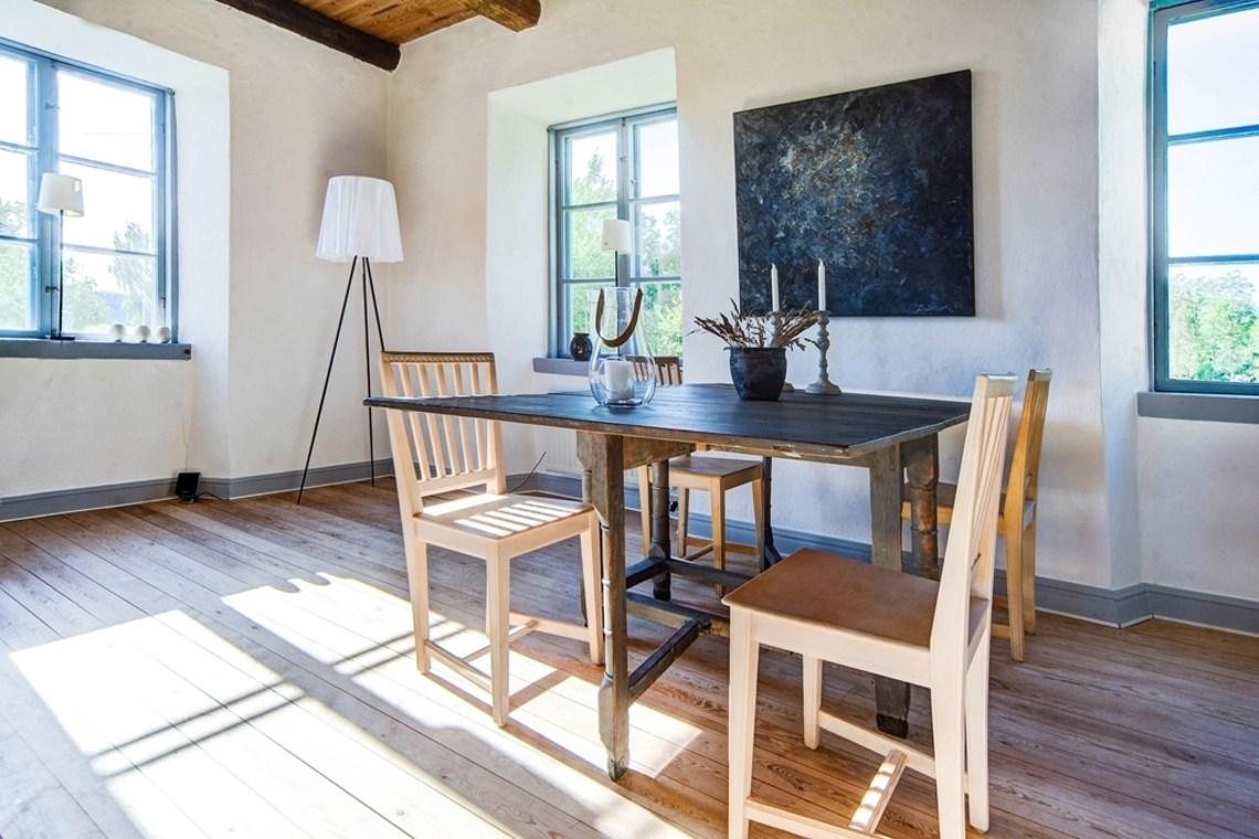 Стол в большой жилой комнате на первом этаже дома. Деревянные полы и перекрытия с открытыми деревянными балками добавляют тепла в интерьер комнаты.