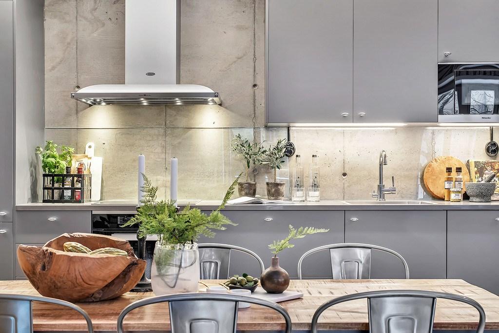 Кухня расположена вдоль столовой. Бетонная стена в районе кухонного фартука закрыта стеклом, которое не скрывает бетонного колорита.