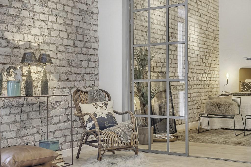 Плетеное кресло естественно смотрится на фоне кирпичной стены.
