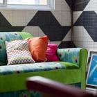 Яркий зеленый диван и тротуарная плитка на стенах гостиной.