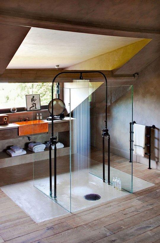 Минималистичная душевая кабина из стекла без рамы не отвлекает внимания от уникального дизайна душа в этой ванной комнате.
