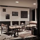Картины в жилой комнате расположены на большом белом экране, который выделяет их на фоне серых стен.