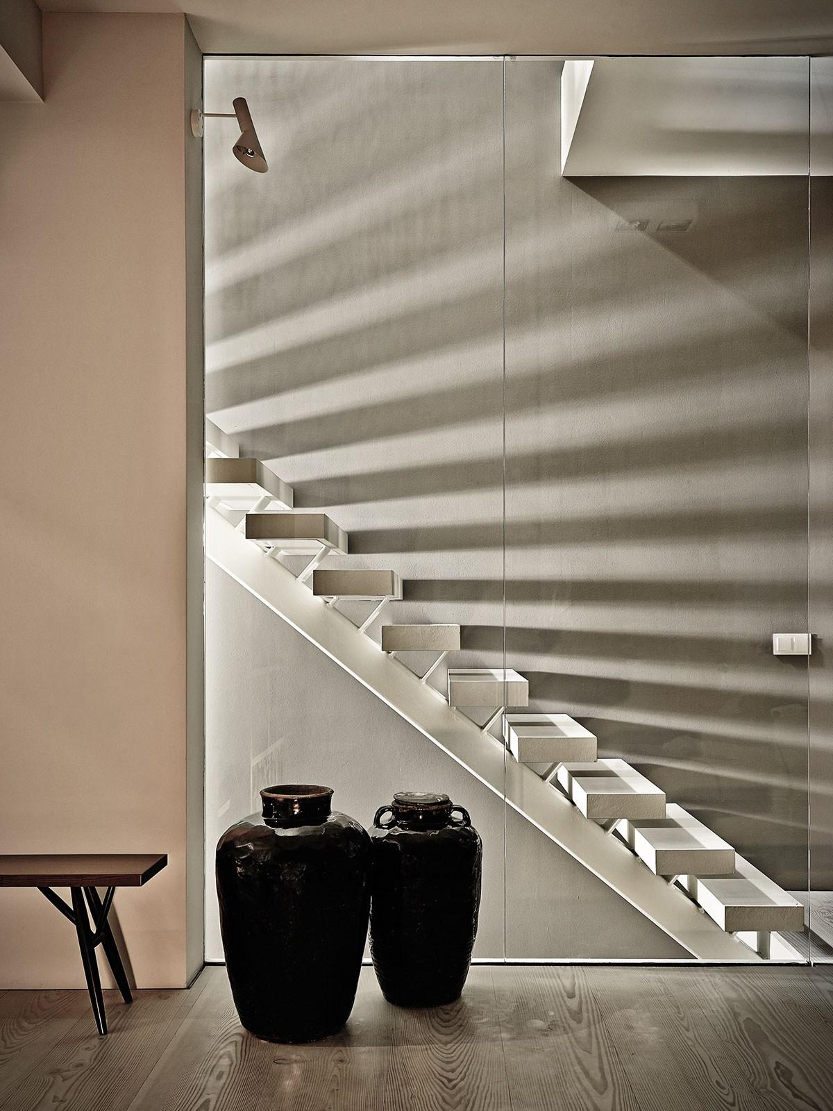 Лестница на второй этаж пропускает свет и создает интересные блики на стене.