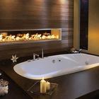 Большая ванная комната больше напоминает спа с гидромассажной ванной и газовым камином. (ванна,санузел,душ,туалет,дизайн ванной,интерьер ванной,сантехника,кафель,интерьер,дизайн интерьера,мебель,камин,очаг,минимализм,современный)