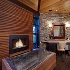 Современная ванна с камином рядом с цинковой ванной и выходом во двор.