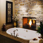 В данной ванной в средиземноморском стиле камин находится прямо рядом с ванной. Сам камин является двусторонним и второй стороной выходит в спальню.