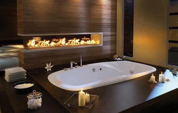 Большая ванная комната больше напоминает спа с гидромассажной ванной и газовым камином.