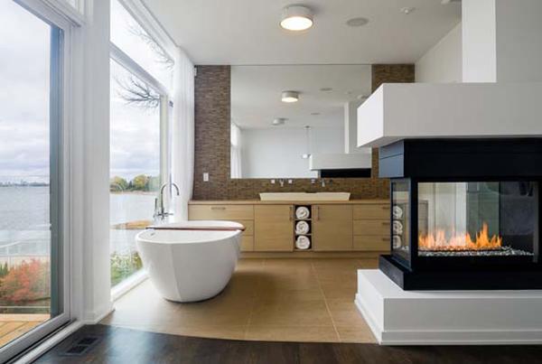 Современная ванна с видом на океан и газовым камином в центре комнаты.