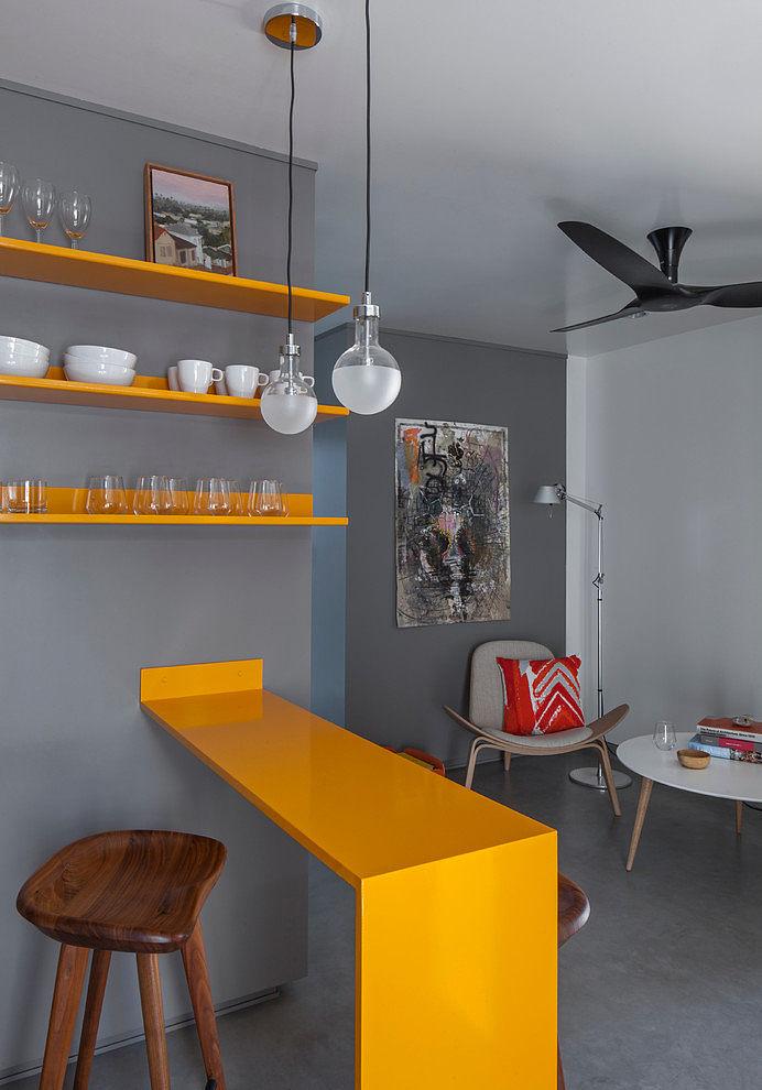 Яркая желтая барная стойка и такие же желтые полочки являются своеобразным украшением и существенно оживляют интерьер квартиры выполненный в серых тонах.